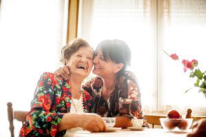 Senior Woman Enjoying a relaxing moment with her Daughter at Home drinking Coffee