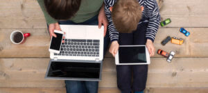 A woman works on her laptop while her son plays on a tablet