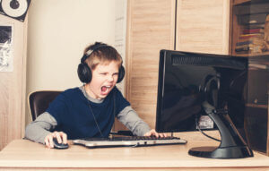 Gaming, entertainment, technology, let's play concept. Angry screaming pre teen boy in headset with pc computer playing game at home