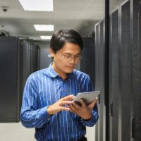 A managed services provider checks a set of servers with a tablet.
