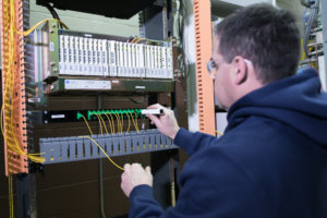 A man works on a fiber switchboard.