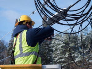 OTELCO engineer working on fiber optic cables.