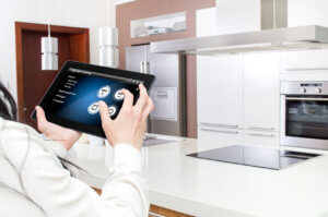 a women controls her kitchen with a tablet.