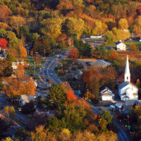 The fall foliage surrounds a quaint New England village in an aerial photogrph