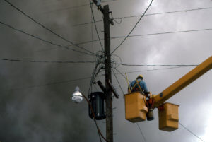 A man works on a utility pole during a fire.
