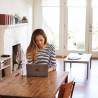 A women sits at a dining room table telecommuting from her laptop.