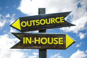 """A wooden sign with arrows facing opposite directions reading """"outsource"""" and """"in-house"""""""