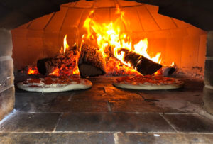 Pizza cook's in a wood fire oven.