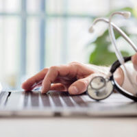 A doctor uses telehealth technology on his laptop.