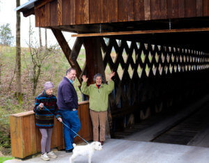 OTELCO Vice President Trevor Jones visits the Easley Covered Bridge with Sharon Cook, Mari Brindle, and little Oscar.