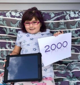 A picture of Abby, a little girl the Grahamtastic Connection supported, holding a piece of paper with the number 2,000 on it.
