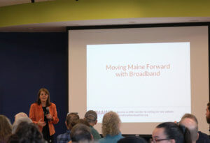 "Commisioner Heather Johnson of the DCED giving the broadband summit keynote address in front of a crowd, with a slide up that reads ""Moving Maine Forward with Broadband."""
