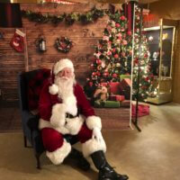 A picture of Santa in front of a Christmas tree and presents during lat year's Festival of Lights