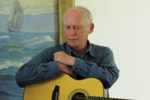 A picture of Archie Fisher holding a guitar in front of a painting