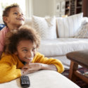 How Much Speed Do You Need: A brother sits on top os his little sister as they watch TV on the Couch
