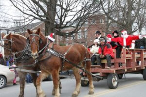 A horse drawn wagon with Santa on it.