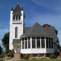 A picture of The First Congregational Church of Gray, UCC. A white chrich sitting on a corner on a sunny day with grass and shrubs around it