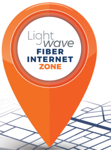 An orange location pin, that reads Lightwave fiber Internet zone in the center, on top of crisscrossing map lines. Click to visit OTELCO's Lightwave locator.