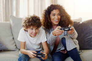 Shot of a young mother and her son playing video games together, using our online gaming safety tips.