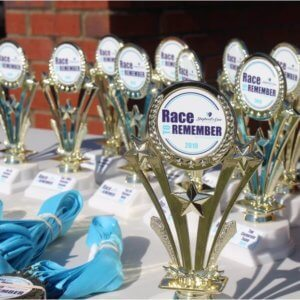 "The awards table at the Race to Remember, with several trophies that say ""A Race to Remember."""
