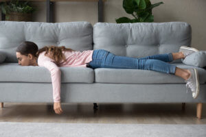 A woman lays face down on a couch, bored form self-isolating at home.