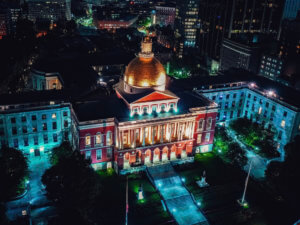 The Massachusetts State House at night, where important broadband legislation and funding has kept the state connected for years
