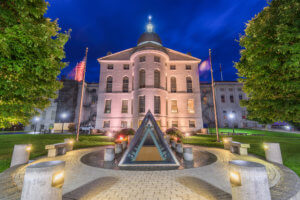 The Maine State House at night where a lot of Broadband Legislation is working their way through the senate and house